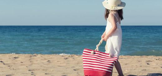 Barn med taske på stranden