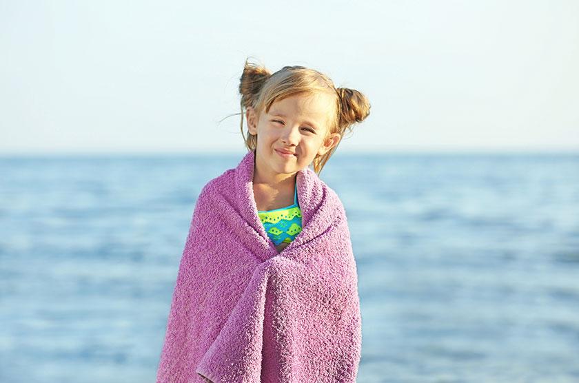 Pige på strand i håndklæde